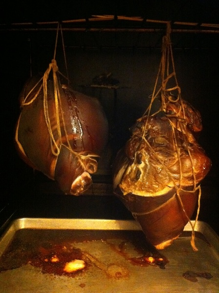 Suckling pig hams coming out of their 12-hour smoke