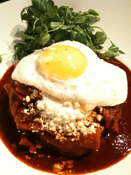 Last plate out of the kitchen at almuerzo (brunch): guajillo chilaquiles w fried egg, pea shoots and queso añejo