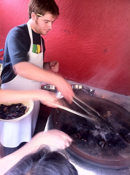 Susana Trilling Oax cooking school: chef Zach darkly toasting chiles for black mole