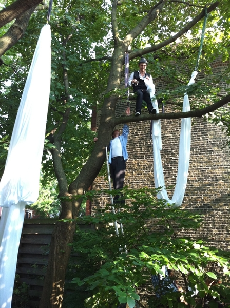 Tony Hernandez and Andy White hanging silks for performers in the trees