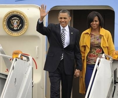 Michelle Obama wearing Rachel Roy Cadmium Trench Coat whilst arriving in NYC. In town for the Met Gala I wonder?