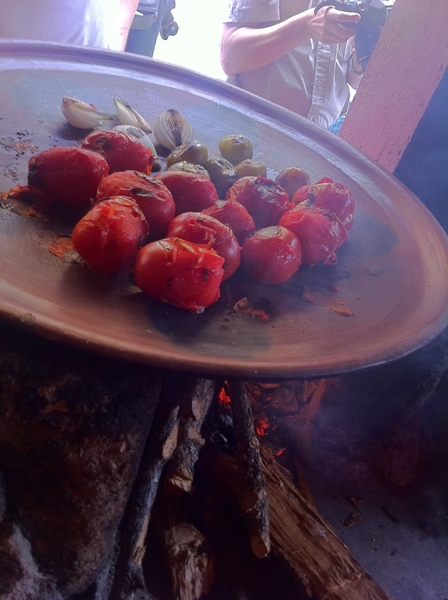 Susana Trilling Oax cooking school: roasting tomatoes/tomatillos for black mole. Clay griddle, wood fire