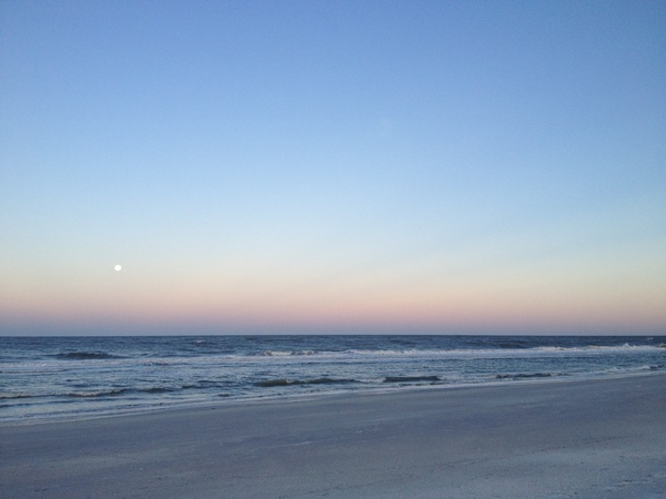 Sunrise on the beach. The moon is still in the sky.